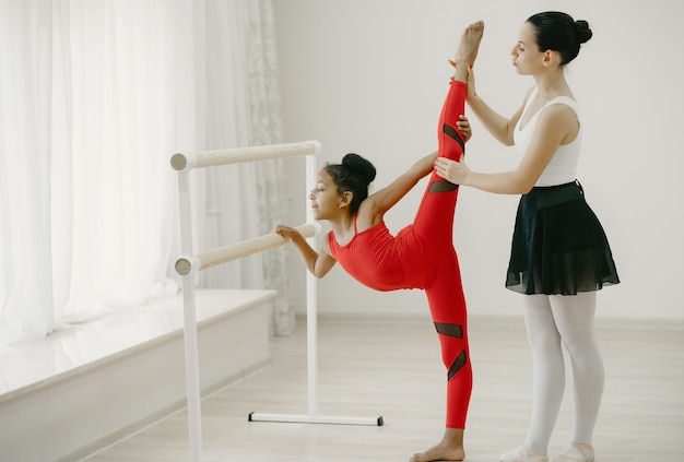 赤いスポーツスーツのかわいい小さなバレリーナ。部屋で踊っている子供。ティーチャーとダンスクラスの子供