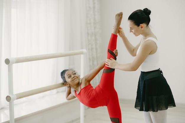 Милая маленькая балерина в красном спортивном костюме. ребенок танцует в комнате. ребенок в танцевальном классе с учителем