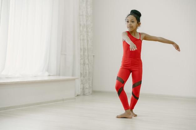 빨간색 spotsuit에 귀여운 작은 발레리나. 아이 방에서 춤을. 댄스 클래스에서 아이.