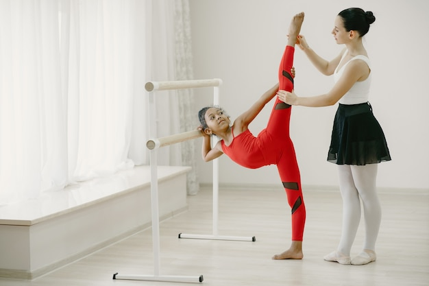 Piccola ballerina sveglia in tuta sportiva rossa. bambino che balla nella stanza. kid in classe di danza con teatcher