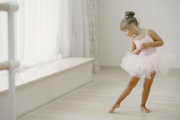 ピンクのバレエ衣装のかわいい小さなバレリーナ。トウシューズを履いた子供が部屋で踊っています。ダンスクラスの子供。
