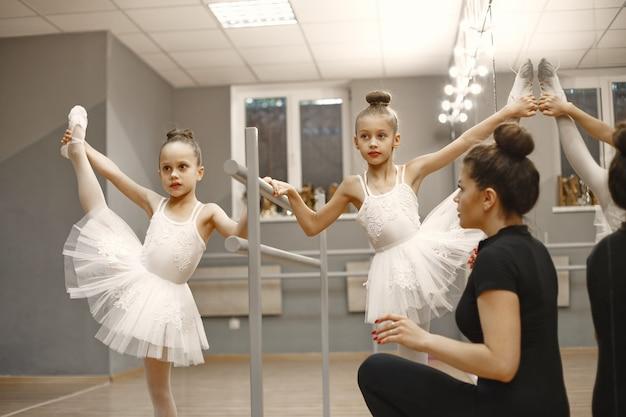 핑크 발레 의상을 입은 귀여운 작은 발레리나. 뾰족 구두를 신은 아이들이 방에서 춤을 추고 있습니다. 선생님과 함께 댄스 클래스에서 아이.