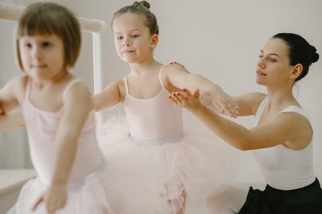 핑크 발레 의상을 입은 귀여운 작은 발레리나. 뾰족 구두를 신은 아이들이 방에서 춤을 추고 있습니다. teatcher와 함께 댄스 클래스에서 아이.