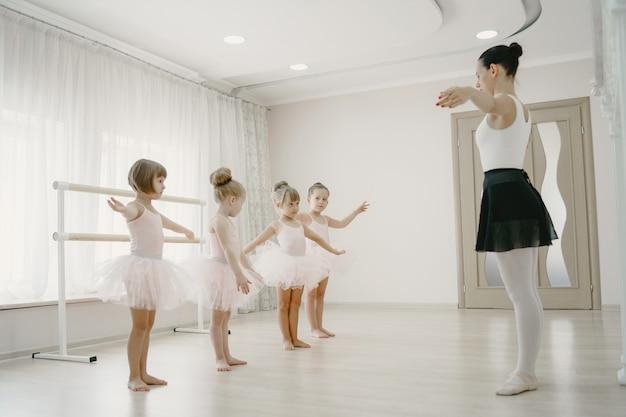 ピンクのバレエ衣装のかわいい小さなバレリーナ。トウシューズを履いた子供たちが部屋で踊っています。ティーチャーとダンスクラスの子供。