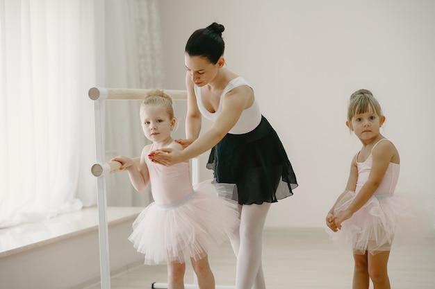 핑크 발레 의상을 입은 귀여운 작은 발레리나. 뾰족한 신발을 신은 아이들이 방에서 춤을 추고 있습니다. teatcher와 함께 댄스 클래스에서 아이.