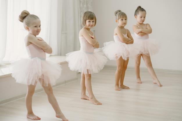 핑크 발레 의상을 입은 귀여운 작은 발레리나. 뾰족 구두를 신은 아이들이 방에서 춤을 추고 있습니다. 댄스 클래스에서 아이.