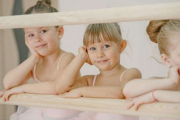 핑크 발레 의상을 입은 귀여운 작은 발레리나. 뾰족한 신발을 신은 아이들이 방에서 춤을 추고 있습니다. 댄스 클래스에서 아이.