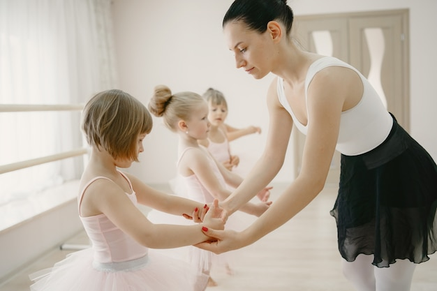 ピンクのバレエ衣装のかわいい小さなバレリーナ。トウシューズを履いた子供たちが部屋で踊っています
