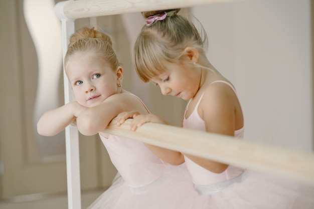 핑크 발레 의상을 입은 귀여운 작은 발레리나. 뾰족 구두를 신은 아이들이 방에서 춤을 추고 있습니다.