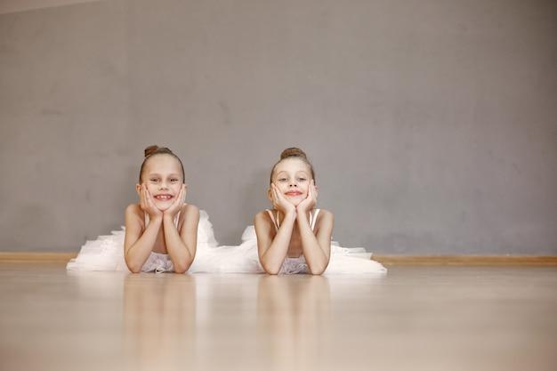 흰색 발레 의상을 입은 귀여운 작은 발레리나. 뾰족 구두를 신은 아이들이 방에서 춤을 추고 있습니다. 댄스 클래스에서 아이.