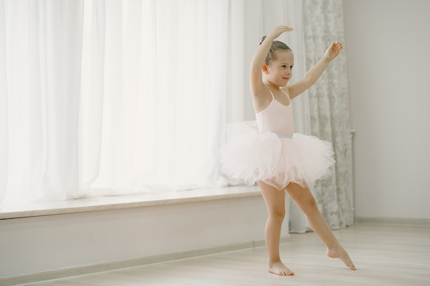 Cute little ballerinas in pink ballet costume. child in a pointe shoes is dancing in the room. kid in dance class.