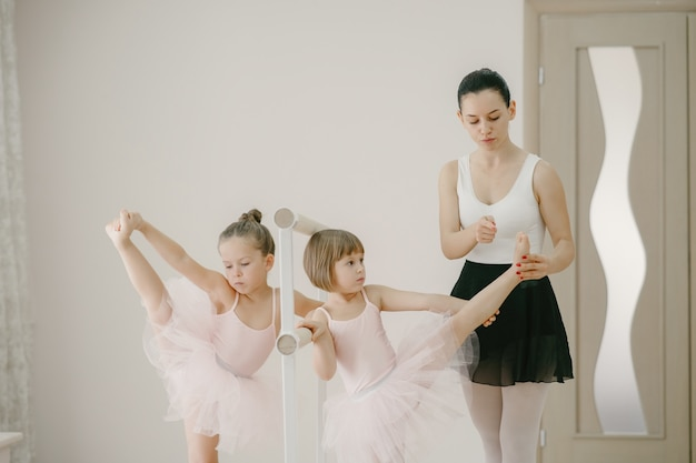Cute little ballerinas in pink ballet costume. children in a pointe shoes is dancing in the room. kid in dance class with teatcher.