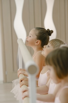 Piccole ballerine carine in costume da balletto rosa. i bambini in scarpe da punta balla nella stanza. kid in classe di danza.