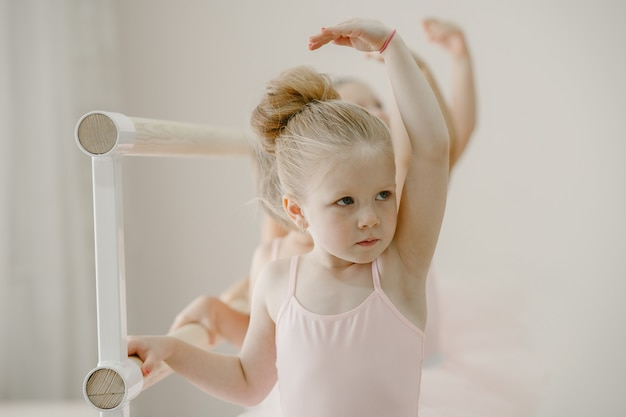 Cute little ballerinas in pink ballet costume. children in a pointe shoes is dancing in the room. kid in dance class.