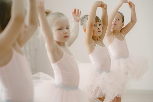 Piccole ballerine carine in costume da balletto rosa. i bambini in scarpe da punta balla nella stanza