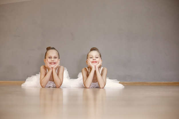 Cute little ballerinas in white ballet costume. children in a pointe shoes is dancing in the room. kid in dance class.