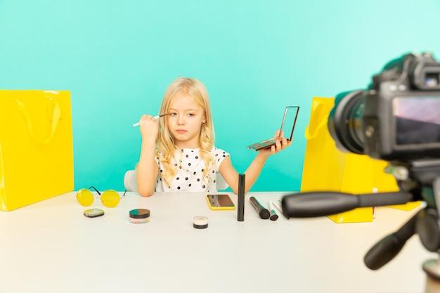 귀여운 뷰티 블로거. 동영상 블로그에 대한 카메라 앞에서 말하는 소녀. 블로거로 일하는 젊은 흑인 여성, 인터넷 비디오 튜토리얼 녹화.