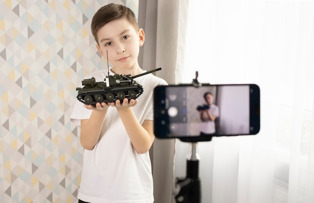 カメラ画面にタイプライターを持ったかわいい小さなブロガー、クローズアップ