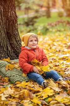 Милый маленький белокурый мальчик веселится на открытом воздухе в парке в осеннее время, сидя в листьях