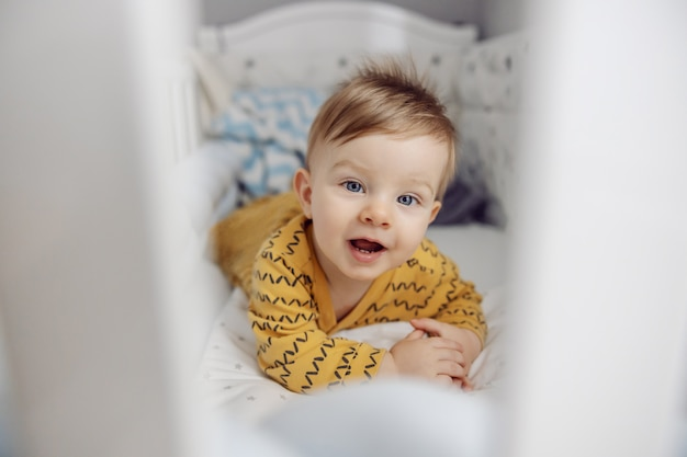 Cute little blond baby boy lying on stomach in crib in the morning