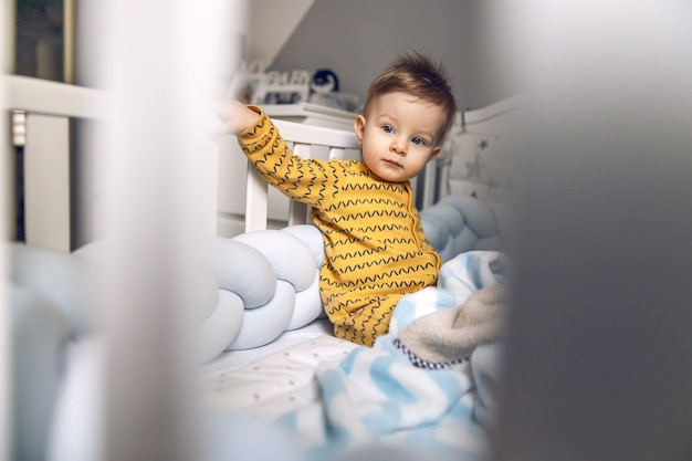 Cute little blond baby boy sitting in his crib in the morning with serious facial expression.