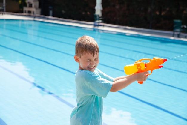 Милый маленький белокурый мальчик веселится в отпуске, играя с водяной пушкой