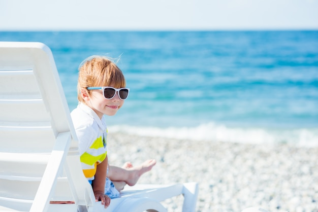 Cute little blond boy in sunglasses sits on a sunbed on the ocean coast