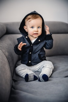 Cute little blond boy with blue eyes sitting on sofa in living room with hoodie on head, having serious facial expression
