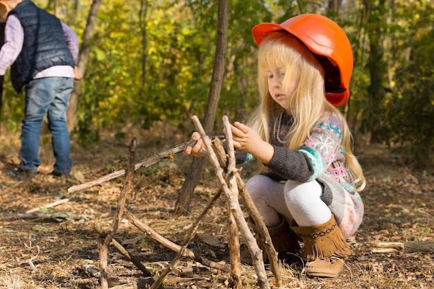 森の中で自然な棒のウィグワムを構築する身をかがめる特大のヘルメットのかわいい小さなブロンドの女の子