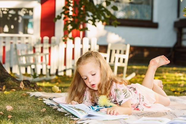 Piccola ragazza bionda sveglia che legge libro fuori sull'erba