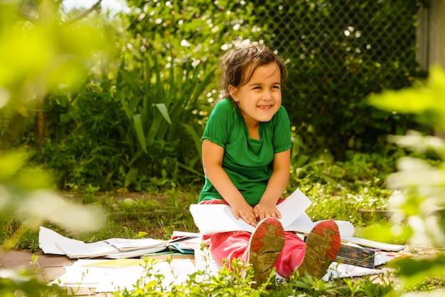 Cute little blond girl reading outside on grass