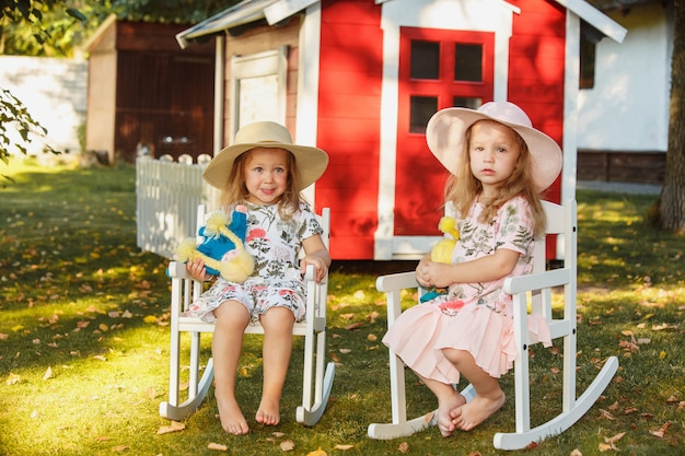 Cute little blond girls in hats sitting on the field with soft toys in summer.