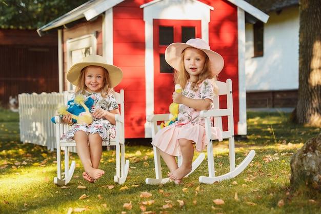 Милые маленькие белокурые девушки в шляпах сидя на поле с мягкими игрушками в лете.