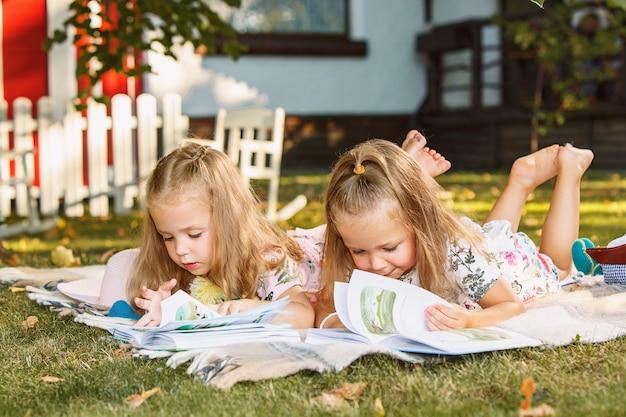 Cute little blond girls reading book outside on grass