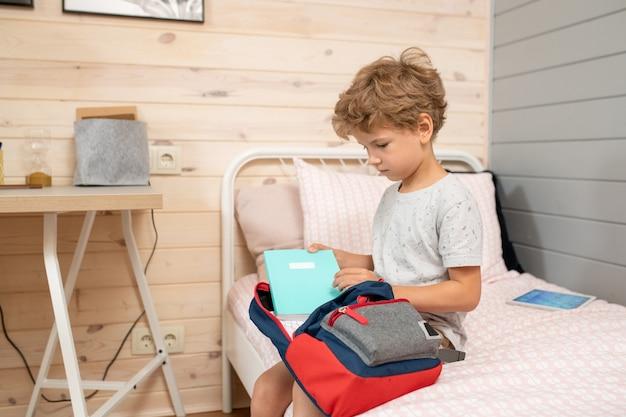 Симпатичный маленький белокурый школьник в повседневной одежде сидит на кровати и собирает книги, тетради и другие школьные принадлежности в рюкзак перед уроками