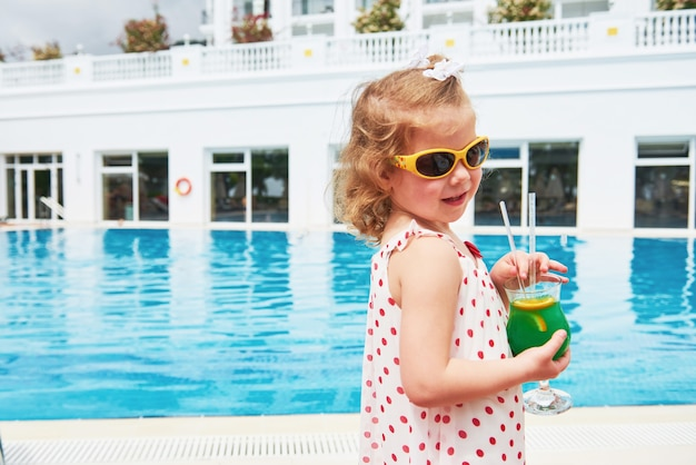 Милая маленькая блондинка у бассейна и держит детский коктейль.