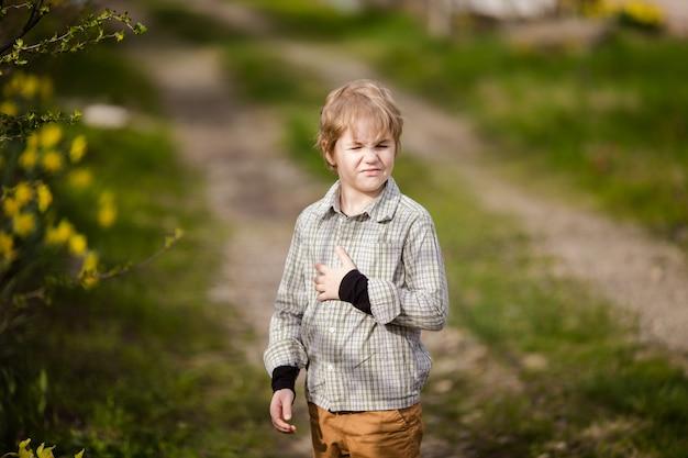 Милая маленькая блондинка мальчик в стране весной с желтыми нарциссами