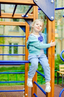 Cute little blonde caucasian girl having fun on a playground outdoors in summer.