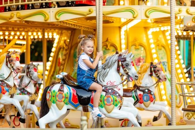 Cute little blonde girl in an amusement park