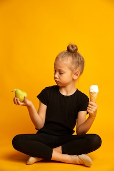 Cute little blonde girl choosing between pear and sweet ice-cream on yellow background