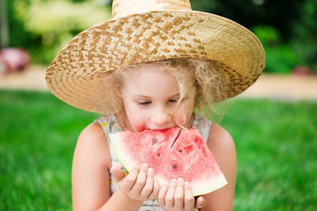 수박을 먹는 귀여운 금발 소녀, 여름철 야외.