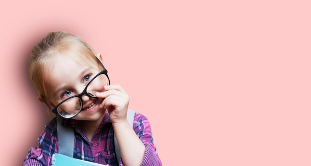 Cute little blonde girl in glasses with a backpack on a pink walll teaching preschoolers concept.