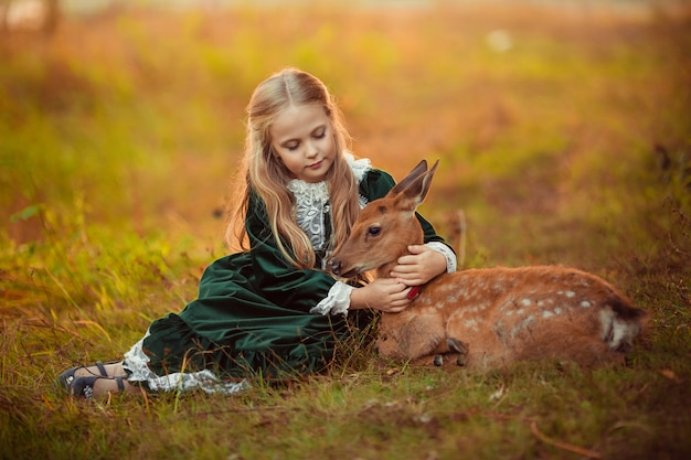 A cute little blonde girl in a green vintage dress sits next to a small sika deer around them yellow beautiful autumn trees