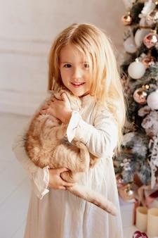 かわいい小さなブロンドの女の子は、クリスマスツリーの近くに赤い猫を保持します