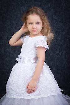 어두운 배경에 아름다운 흰색 드레스를 입은 귀여운 금발 소녀. 여섯 살짜리 아름다운 소녀