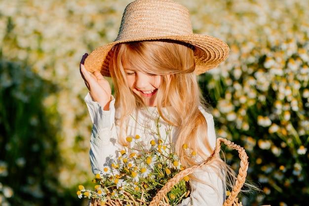 Милая маленькая блондинка в хлопковом платье и соломенной шляпе гуляет по полю ромашек и собирает их в корзину