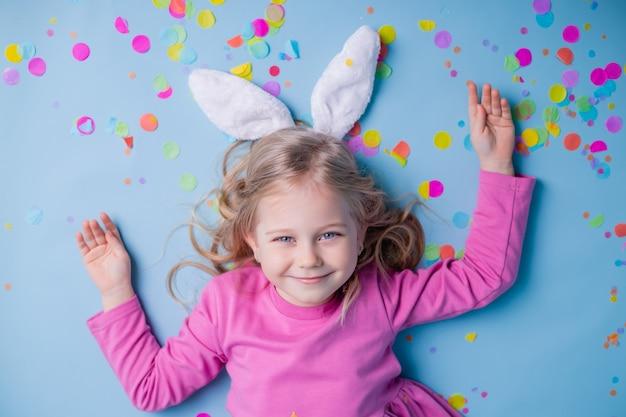 Милая маленькая блондинка в ушах пасхального кролика в розовом платье на синем фоне.