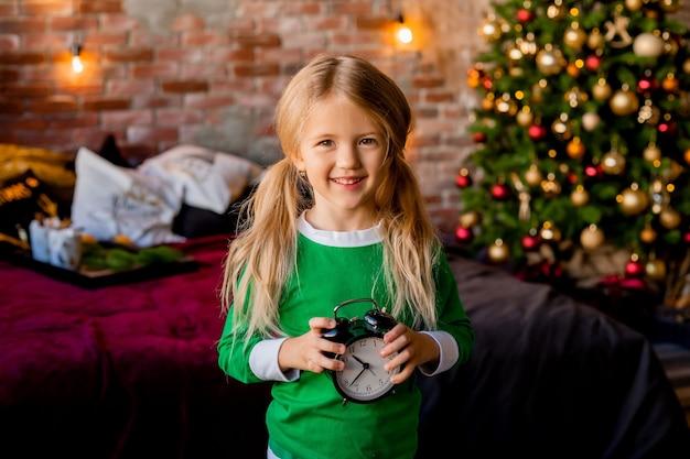 Милая маленькая блондинка в пижаме возле елки