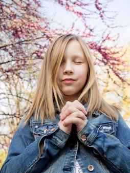 祈っているかわいいブロンドの女の子
