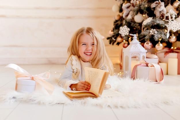 귀여운 금발 소녀는 크리스마스 트리 근처 집에서 책을 읽습니다.